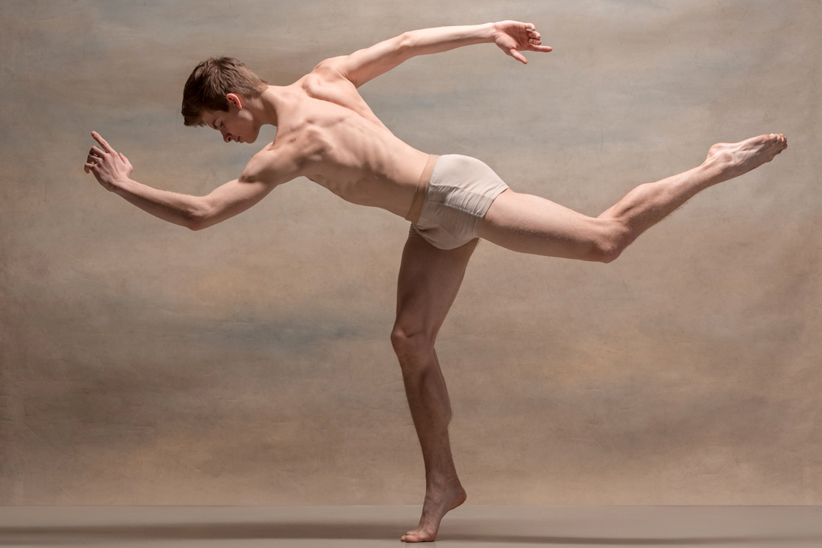 the-male-ballet-dancer-posing-over-gray-P9JN9XF